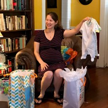 Baby Shower - Paulette holding onesies